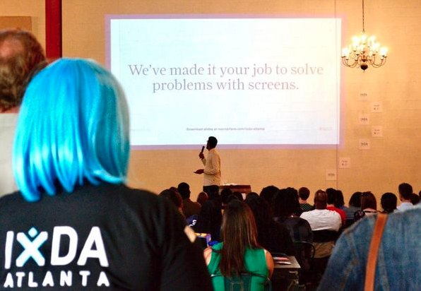 Image: Woman in foreground with IxDA Atlanta shirt, seated crowd, and presenter on stage in background with screen